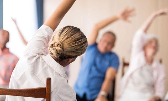 пожилые люди делают гимнастику с инструктором