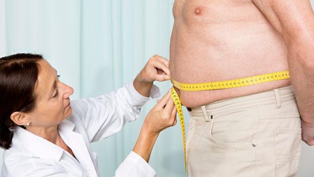 врач измеряет талию у мужчины с лишним весом