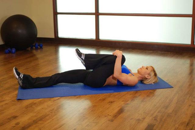 подтягивание колен к груди из положения лежа на спине